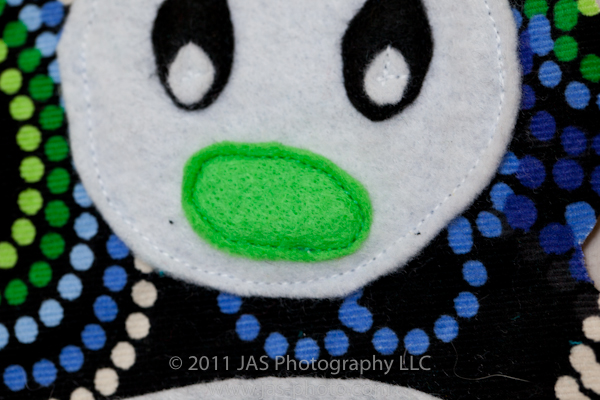 straight stitch applique of nose on stuffed penguin