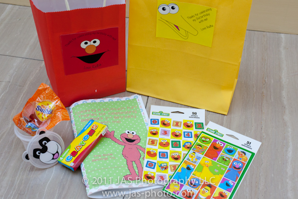 gift bag ideas for sesame street elmo party theme with coloring book, stickers, and fruit snacks